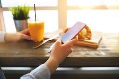 Kvinnan i ett hemtrevligt kafé nära ett stort fönstersammanträde på tabellen och leder konversationen på sociala nätverk med din  Arkivbild