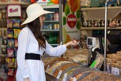 Kvinnan i ett lager är köpandeprodukter Royaltyfri Fotografi