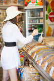 Kvinnan i ett lager är köpandeprodukter Arkivbilder