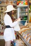 Kvinnan i ett lager är köpandeprodukter Arkivfoto