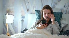 Kvinnan i exponeringsglas ligger i en säng och använder en smartphone för läggdags