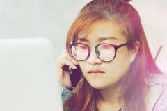 Kvinnan i exponeringsglas som ser datoren och, väntar på mobiltelefonen royaltyfria bilder