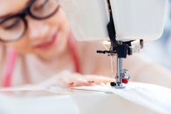 Kvinnan i exponeringsglas syr på symaskinen Fotografering för Bildbyråer