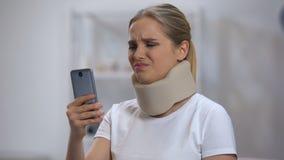 Kvinnan i för krageläsning för skum cervikalt meddelande på mobiltelefonen som känner sig smärtar i hals stock video