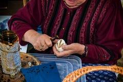Kvinnan i folkdräkt målar det traditionella easter ägget Royaltyfria Foton