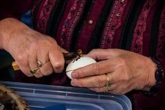 Kvinnan i folkdräkt målar det traditionella easter ägget Royaltyfri Fotografi