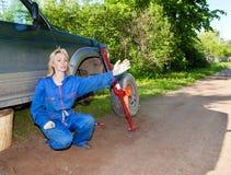 Kvinnan i funktionsdugliga overaller försöker att byta ut ett hjul på enväg bil och frågar hjälpen Arkivfoton