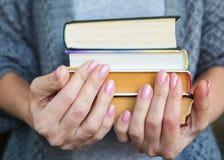 Kvinnan i grå kläder rymmer fyra böcker i hand royaltyfria foton