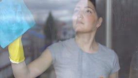 Kvinnan i gula handskar tvättar fönstret med en blå trasa lager videofilmer