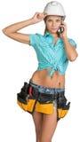 Kvinnan i hård hatt och hjälpmedlet kuter att kalla på mobil Royaltyfri Bild