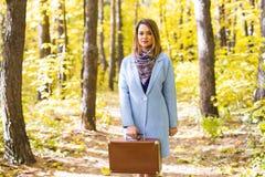 Kvinnan i höst parkerar att gå med resväskan arkivfoton