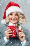 Kvinnan i hatt för santa ` s dricker kaffe Arkivbilder