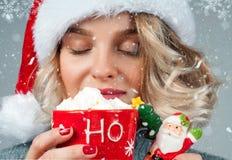 Kvinnan i hatt för santa ` s dricker kaffe Royaltyfria Bilder