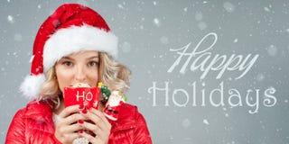 Kvinnan i hatt för santa ` s dricker kaffe lycklig ferie Arkivbild
