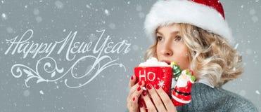 Kvinnan i hatt för santa ` s dricker kaffe lyckligt nytt år Royaltyfria Bilder