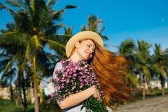 Kvinnan i hatt med blommor känner sig fritt Royaltyfria Bilder