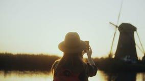 Kvinnan i hatt sitter på kajen för solnedgångbygdsjön Flickan tar ett gammalt väderkvarnfoto genom att använda hennes smartphone  lager videofilmer