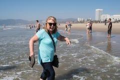 Kvinnan i hennes 60-tal promenerar shorelinen i Santa Monica California och att ha en rolig tid med henne skor av fotografering för bildbyråer