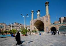Kvinnan i hijab rusar från imamen Khomeini Mosque som tidigt byggs i 18th med två minaret Royaltyfria Bilder