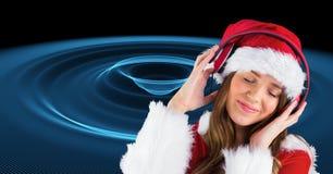Kvinnan i jultomten kostymerar att lyssna till musik på hörlurar arkivbild