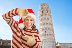 Kvinnan i jultomtenhatt som inramar med händer nära benägenhet, turnerar av Pisa Royaltyfri Fotografi