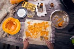 Kvinnan i kökdanande förbereder en paj med pumpa arkivfoto