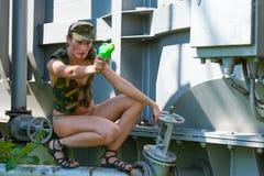 Kvinnan i kamouflage skjuter från en vattenpistol Arkivfoton