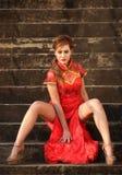 Kvinnan i kinesisk klänning i sexigt poserar Fotografering för Bildbyråer