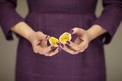 Kvinnan i klänning för ` s för violett 50 räcker att rymma några passionfrukter Arkivfoto