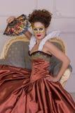 Kvinnan i klänningen av den barocka stilen med en fan Arkivfoton