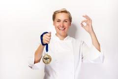 Kvinnan i kockdräkt med perfekt undertecknar upp och medaljen för det första priset Royaltyfri Fotografi
