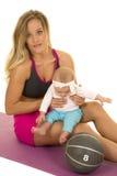 Kvinnan i konditiondress sitter, och hållen behandla som ett barn vid medicinbollen Fotografering för Bildbyråer
