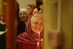 Kvinnan i kyrkan Tro farmodern Äldre kvinna med en stearinljus Arkivbilder
