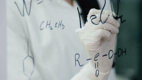 Kvinnan i labb skriver formel på det glass brädet arkivfilmer