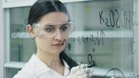 Kvinnan i labb skriver formel på det glass brädet stock video