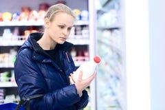 Kvinnan i livsmedelsbutikinnehav mjölkar Arkivbild