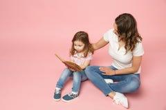 Kvinnan i ljus kläder har den roliga lästa boken med barnet behandla som ett barn flickan Moder dotter för liten unge som isolera royaltyfri bild