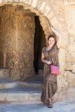 Kvinnan i long tänder klänningen som står nära forntida båge Arkivbild
