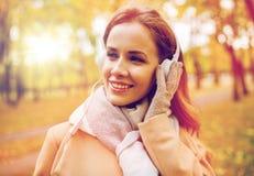 Kvinnan i lyssnande musik för hörlurar på hösten parkerar Royaltyfri Bild