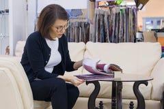 Kvinnan i möblemanglager väljer tyg för stoppningen av soffan, fåtöljer arkivbilder
