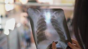 Kvinnan i medicinsk klinik ser till bilden av lungor, stödröntgenstrålar arkivfilmer