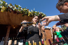 Kvinnan i nationell georgisk dräkt häller vin in i ett exponeringsglas under festival Arkivbild