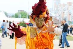Kvinnan i ovanlig maskering poserar under gatateatrar visar på nätter för festivalen för öppen luft vita Royaltyfri Bild