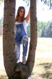 Kvinnan i overaller står mellan trädstammar Royaltyfri Fotografi