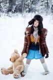 Kvinnan i pälslag och ushankaen med björnen på vit snö övervintrar bakgrund Arkivfoto
