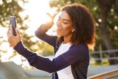 Kvinnan i parkerar utomhus genom att använda mobiltelefonen gör selfie med fred att göra en gest fotografering för bildbyråer