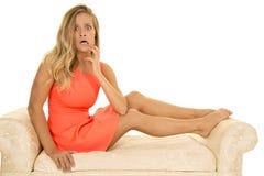 Kvinnan i röd klänning sitter på den stressade vita soffan Arkivbild