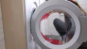 Kvinnan i röda gummihandskar tvättar en tvättmaskin med svampen arkivfilmer