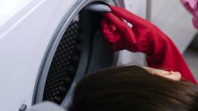 Kvinnan i röda gummihandskar tvättar en tvättmaskin med svampen stock video
