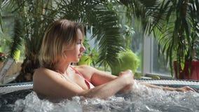 Kvinnan i rosa bikini lägger i det jacuzzy i storgubbeSpa-salong stock video